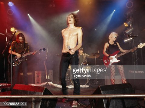 Rock band performing on stage fronted by bare chested man