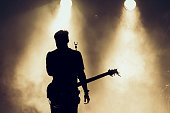 Rock band performs on stage. Guitarist plays solo. silhouette of guitar player in action on stage in front of concert crowd. Smoke. Light