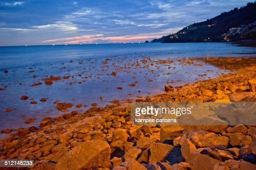 rock beach in Phuket, Thailand at sunset.
