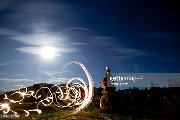 Rock cairn with light painting next to it and full moon in background in Idaho.