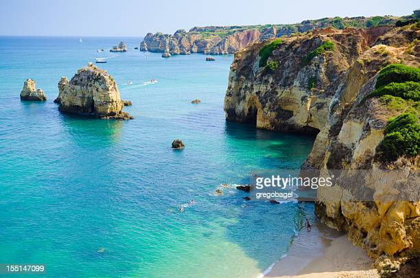 Rock cliffs bordering a teal sea in Lagos, Algarve, Portugal