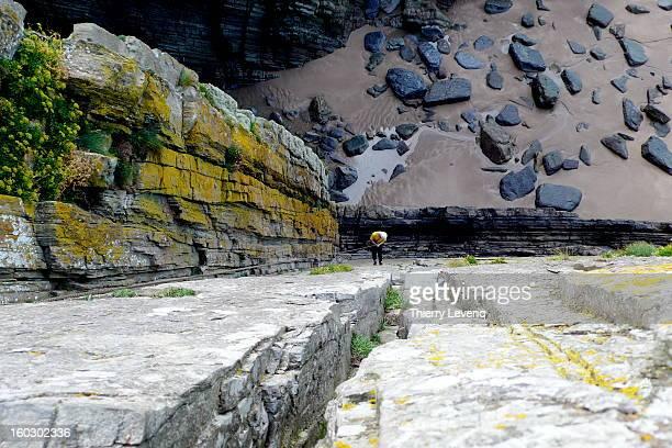 A rock climber abseiling down a sea cliff
