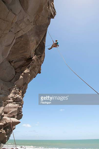 Rock climber abseiling jagged cliff