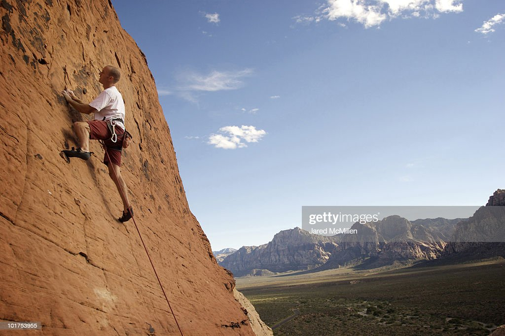 A rock climber ascends a red rock face in Nevada.