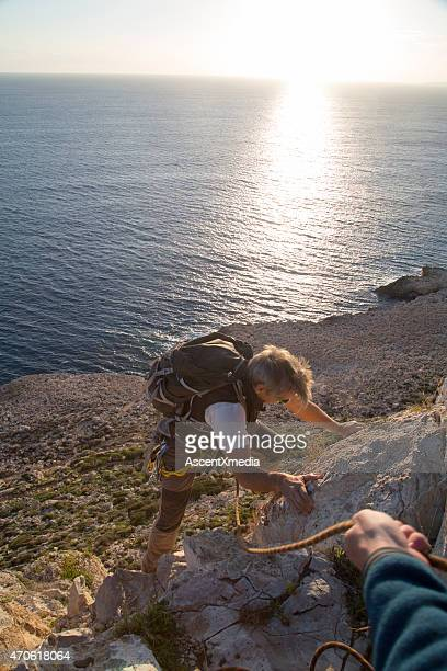 Rock climber ascends rock cliff above sea