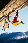 Rock climber bivouaced in his portaledge on an overhanging cliff.