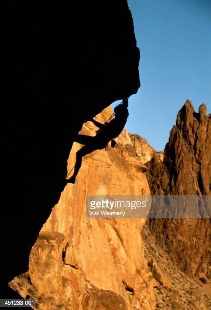 Rock climber climbing up rock overhang, silhouette