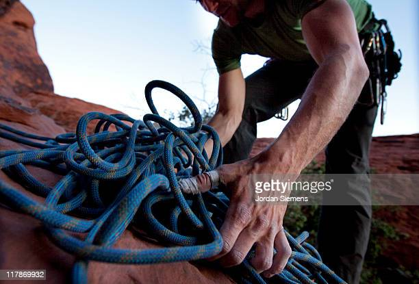 Rock climber coiling rope.