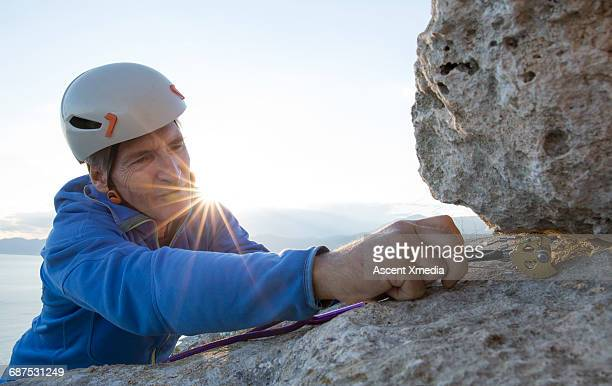 Rock climber places gear in crack, for protection
