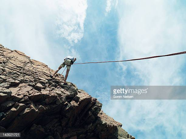 Rock climber rappelling down rock face