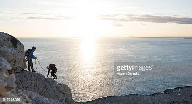 Rock climbers ascend rock ridge above sea