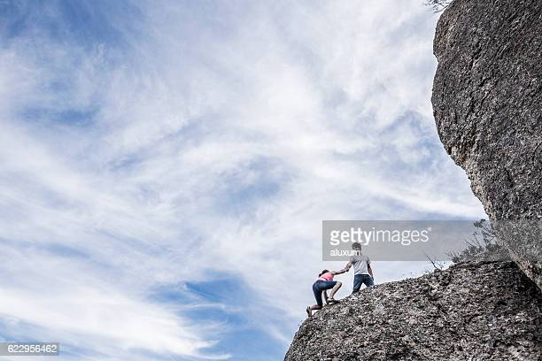 Rock climbers helping each other