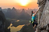 Female extreme climber conquers steep rock against the sunset over the river. China, typical Chinese landscape with mountains and river