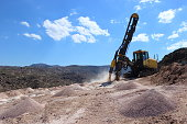 Rock driller working in open quarry