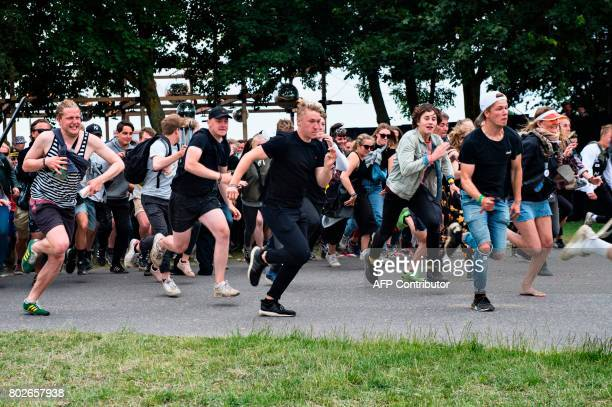 Rock fans rush through the gate during the opening of the Roskilde Festival on June 28 2017 in Roskilde some 30 km west of Copenhagen 90000 rock fans...