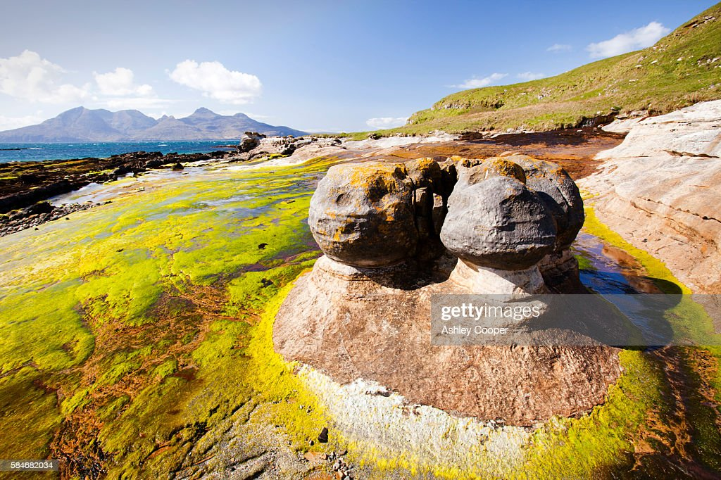 Rock formations and sea weed at the Bay of Laig at Cleadale on the Isle of Eigg, looking towards the Isle of Rhum, Scotland, UK.