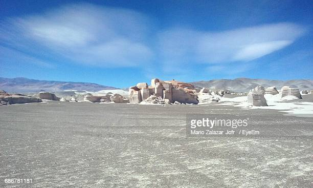 Rock Formations On Field Against Blue Sky On Sunny Day