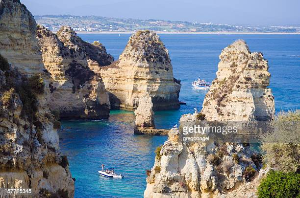 Rock formations with boat at Lagos, Portugal in Algarve region