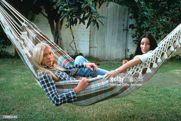 Rock guitarist Gregg Allman and enetertainer Cher pose for a portrait in a hammock at their home on October 30 1977 in Beverly Hills California