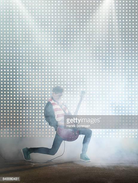rock guitarist in front of lightwall