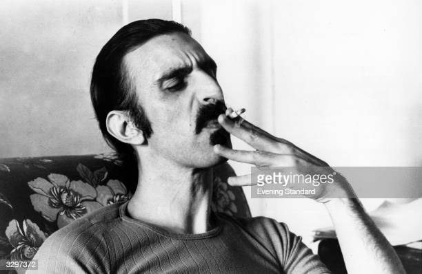 Rock musician avant garde composer writer and musicologist Frank Zappa enjoying a cigarette