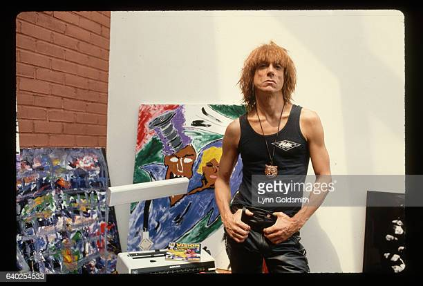 Rock musician Iggy Pop standing with some art work in the background Undated photograph