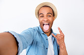 Rock n roll babe! Attractive young mulatto mixed raced guy is posing on the camera, so playful. In casual wear, on pure white background, showing rock sign with tongue out