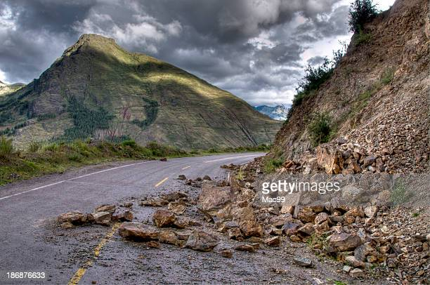 Rock slide with damage on the road during a storm