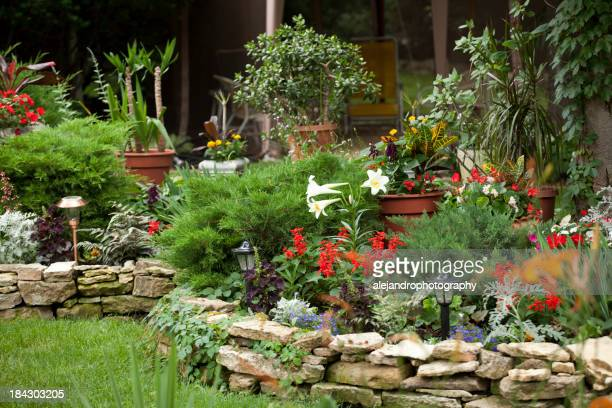 Rock walled flower filled landscape on edge of green lawn