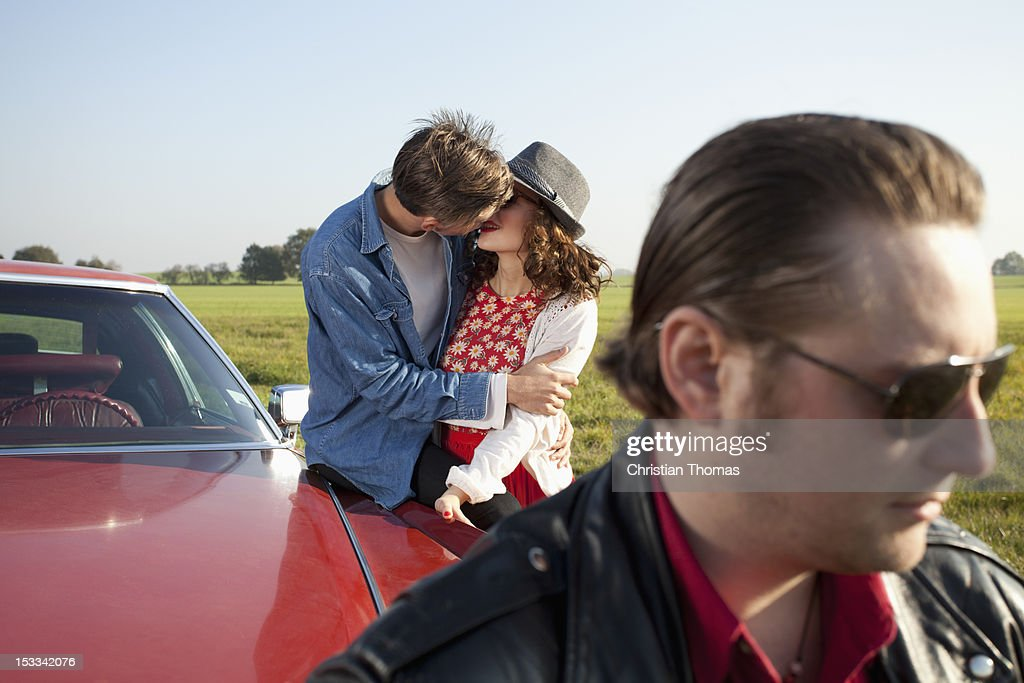 A rockabilly couple kissing while leaning on a vintage car, man in foreground