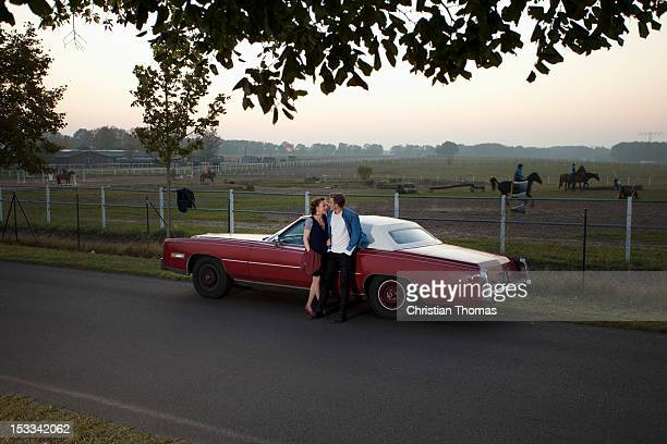 A rockabilly couple leaning against a vintage car in the country