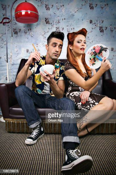 Rockabilly Couple Sitting at Home Eating with Chopsticks on Couch