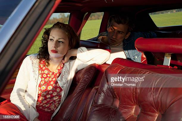 A rockabilly woman and man sitting in a vintage car