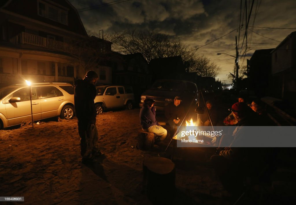 Rockaway residents gather around a fire following Superstorm Sandy at Rockaway Beach on November 3, 2012 in the Queens borough of New York City. Lights from the center of the city can be seen in the distance. Most of the Rockaway Peninsula remains without power as colder weather arrives. With the death toll currently over 90 and millions of homes and businesses without power, the US east coast is attempting to recover from the effects of floods, fires and power outages brought on by Superstorm Sandy.