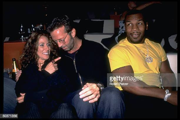 Rockers Sheryl Crow Eric Clapton chatting while sitting w boxer Mike Tyson at concert sponsored by Giorgio Armani to celebrate opening of his new...