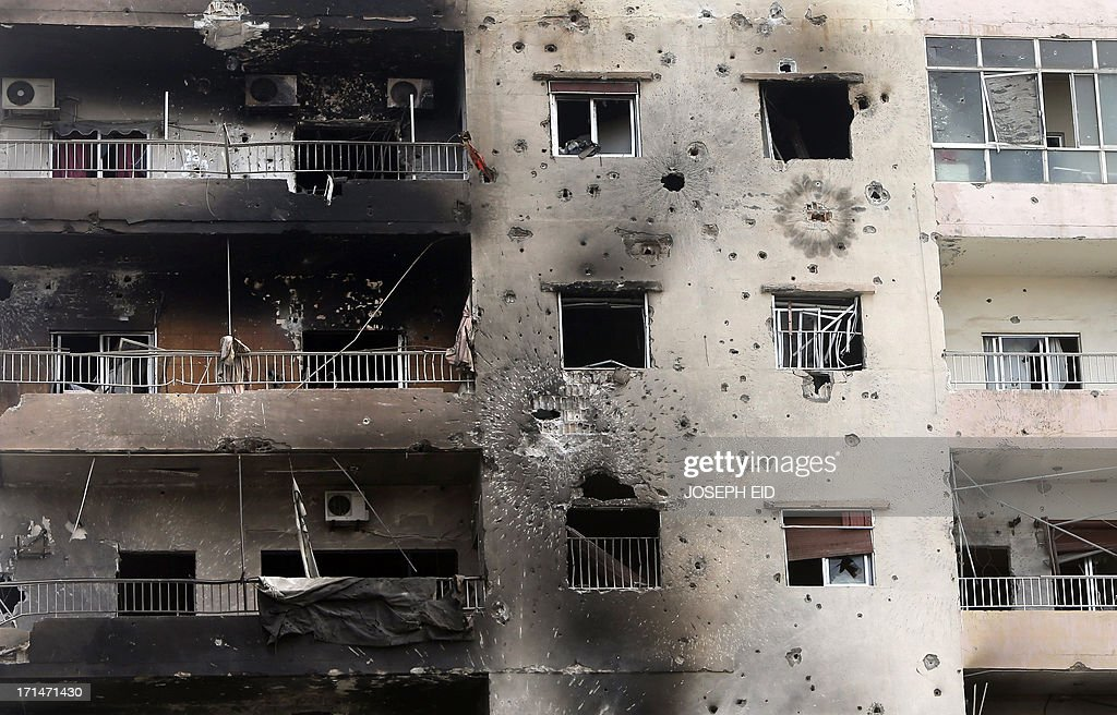 A rocket and bullet riddled building is seen behind the Bilal bin Rabah mosque in the Abra district of the southern city of Sidon on June 25, 2013, after troops seized control of the headquarters of a radical Sunni sheikh whose supporters battled the army for two days, killing 16 soldiers. AFP PHOTO/JOSEPH EID