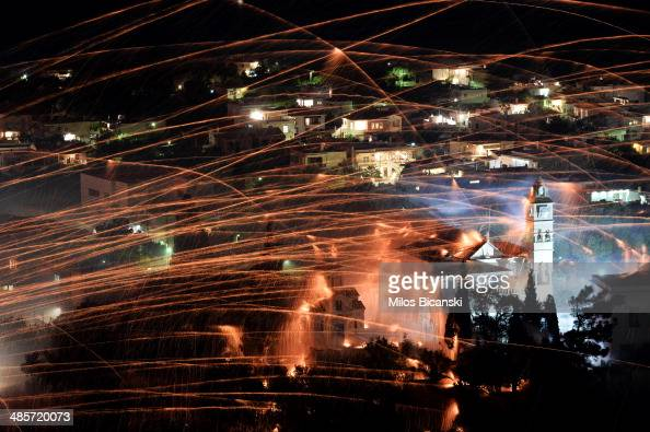 Rockets fly over the bell tower of Panagia Erithiani church during Greek Orthodox Easter celebrations on the eastern Aegean island of Chios late on...