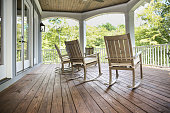 Rocking chairs grace a upper porch in a large lake front home in the Southern USA.