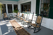 many wood and wicker rocking chairs on a large outdoor front porch.  The porch is wood which has been painted and there is a carpet runner.  The house is white with green shutters.