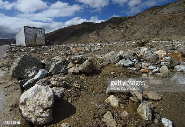Rocks are seen around vehicles stuck in a road after being trapped by a mudslide on California Highway 58 in Mojave California on October 16 after...