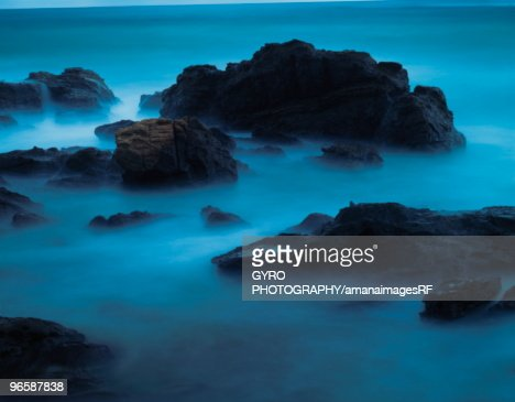 Rocks in sea rising out of fog : Stock Photo
