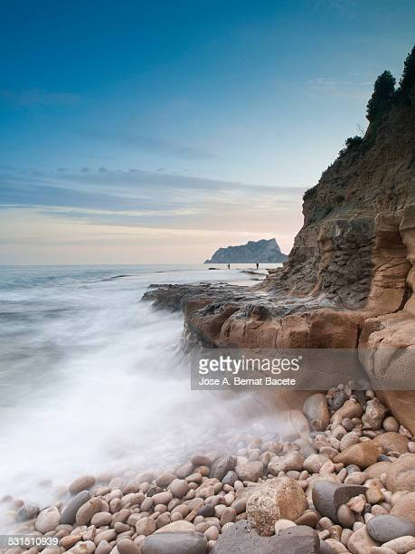Rocks of a marine cliff with the waves in movement