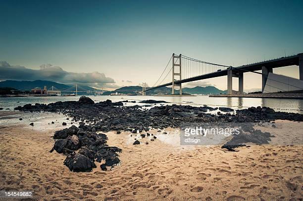 Rocks on beach under bridge