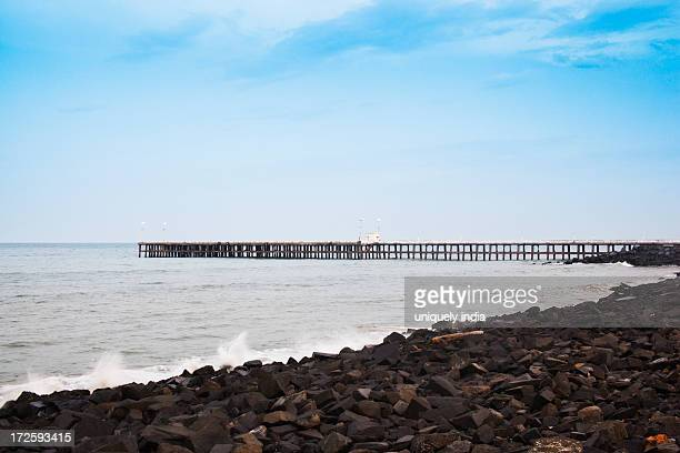 Rocks on beach with pier in the background, Pondicherry, India