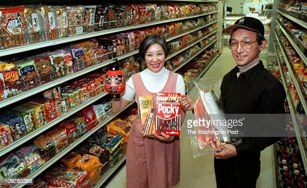 02/02/98 Rockville MD Japanese Food Market Daruma Fumiko and Yasutoshi Yokoyama are shwon in their food market She holding popular Japanese snacks...