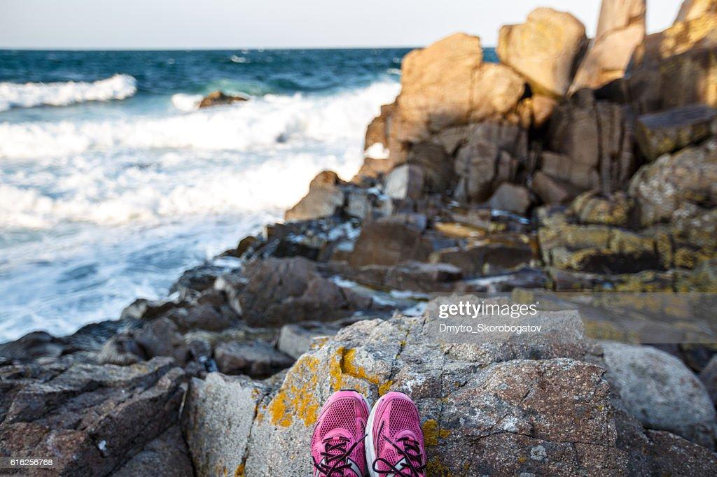 rocky beach rocks with purple sneakers : Foto de stock