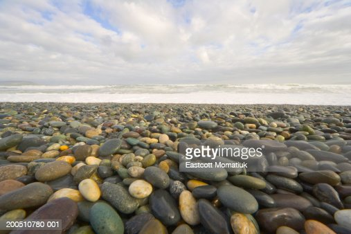 Rocky beach with waves breaking in background : Stock Photo