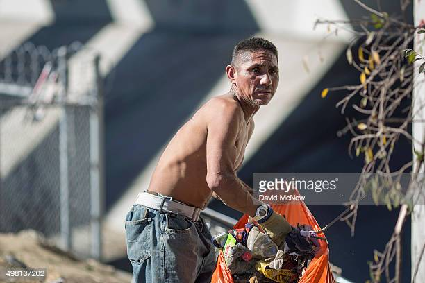 Rocky cleans up the encampment of homeless friends who are faced with imminent eviction while they are away near the concreted channel of the Arroyo...