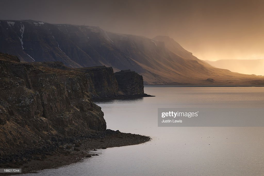 Rocky cliffs line lake during golden sunset : Stock Photo