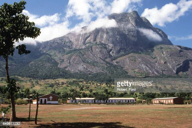 Rocky cliffs of Mulanje Massif and Forest Reserve rising behind rural village in southern Malawi Africa